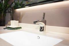 在一个白色水槽的豪华龙头搅拌器在一个美丽的卫生间里,浅景深,毛巾,玻璃,辅助部件 图库摄影