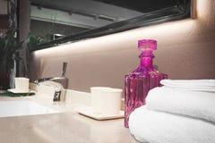 在一个白色水槽的豪华龙头搅拌器在一个美丽的卫生间里,浅景深,毛巾,玻璃,辅助部件 库存照片