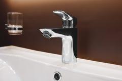 在一个白色水槽的豪华龙头搅拌器在一个美丽的卫生间里 库存图片