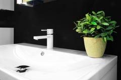 在一个白色水槽的豪华龙头搅拌器在一个美丽的黑暗的卫生间里 库存图片