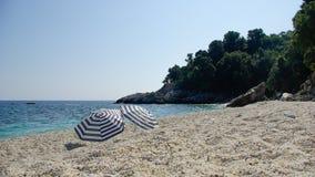 在一个白色海滩的两把伞 库存图片