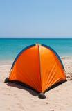 在一个白色海滩的橙色帐篷 库存图片