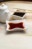 在一个白色盘和筷子的酱油 免版税库存照片