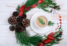 在一个白色盘的一个热奶咖啡杯子与在桌上的新的装饰 免版税库存照片