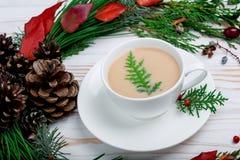 在一个白色盘的一个热奶咖啡杯子与在桌上的新的装饰 库存图片