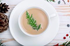 在一个白色盘的一个热奶咖啡杯子与在桌上的新的装饰 免版税库存图片
