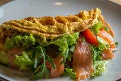 在一个白色盘的法国煎蛋卷 煎蛋卷用法语与沙拉冰山、三文鱼和绿色 饮食煎蛋卷用草本 图库摄影