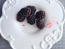 在一个白色盘的黑莓 库存图片