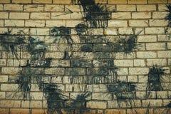 在一个白色砖墙上的黑色污点 免版税库存图片