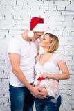 在一个白色砖墙附近的年轻人怀孕的夫妇有一个小儿童圣诞老人帽子的 库存图片
