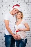 在一个白色砖墙附近的年轻人怀孕的夫妇有一个小儿童圣诞老人帽子的 免版税库存照片