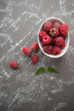 在一个白色碗的成熟莓在与scat的一张灰色石桌上 库存图片