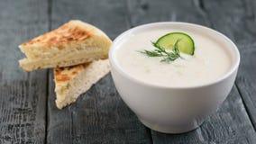 在一个白色碗的新近地做的tzatziki用在一张黑暗的木桌上的面包 免版税库存图片