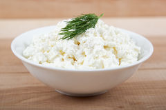 在一个白色碗的新鲜的酸奶干酪在一个木板 免版税库存图片