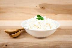 在一个白色碗的新鲜的酸奶干酪在一张木桌上 库存照片