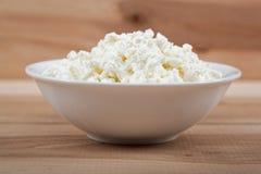 在一个白色碗的新鲜的酸奶干酪在一张木桌上 免版税库存照片