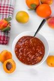 在一个白色碗的杏子果酱用在白色木背景的新鲜的杏子 免版税库存照片