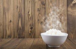 在一个白色碗的热的蒸的米在木背景 库存照片