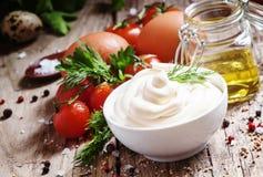 在一个白色碗的自创蛋黄酱调味汁,有橄榄油的, e瓶子 库存照片