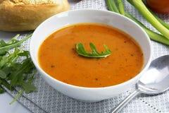 在一个白色碗的蕃茄奶油色汤有芝麻菜的装饰 免版税库存照片