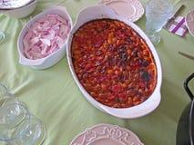 在一个白色碗的被烘烤的豆在一张绿色桌布 免版税库存图片