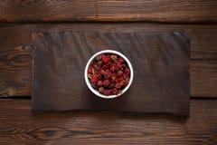 在一个白色碗的野玫瑰果莓果在一块木平板 木背景 免版税库存照片