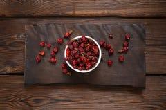 在一个白色碗的野玫瑰果莓果在一块木平板 木背景 免版税库存图片
