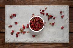 在一个白色碗的野玫瑰果莓果在一块混凝土板 可能 免版税库存图片