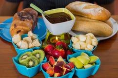 在一个白色碗里面的可口巧克力涮制菜肴用被分类的果子,草莓、梨、猕猴桃、苹果和片断  图库摄影
