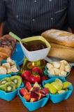 在一个白色碗里面的可口巧克力涮制菜肴用被分类的果子,草莓、梨、猕猴桃、苹果和片断  库存图片