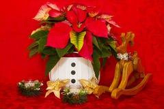 在一个白色篮子的一品红与蜡烛和驯鹿 库存照片