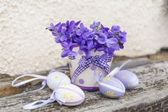 在一个白色篮子的小复活节彩蛋与紫罗兰 库存图片
