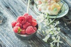 在一个白色罐的成熟新鲜的莓在与小白色铁线莲属的一个土气样式开花特写镜头 库存照片