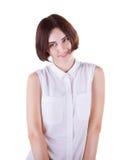 在一个白色背景特写镜头一件白色女衬衫的和有相当迷人的微笑的隔绝的一个害羞,浪漫和嬉戏的少妇 库存图片