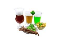 在一个白色背景琥珀色的绿色阵营的啤酒与一开胃菜三叶草圣帕特里克` s天 库存图片