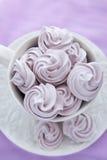 在一个白色茶杯的蛋白甜饼在淡紫色颜色背景 库存照片