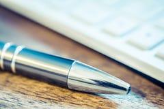 在一个白色键盘前面的镀铬物铅笔在木表上 库存照片
