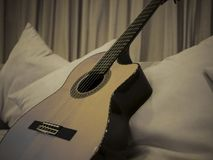 在一个白色长沙发的一把可爱的古典吉他 库存照片