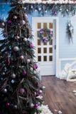 在一个白色门的背景的装饰的假日树 库存照片