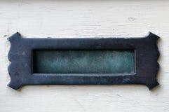 在一个白色门的铜绿黄铜信箱 库存图片