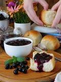 在一个白色陶瓷碗和金黄小圆面包的莓果果酱 免版税库存照片