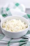 在一个白色陶瓷碗的有机酸奶干酪在厨房用桌上 乳制品健康早餐 免版税库存图片