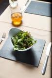 在一个白色陶瓷碗的沙拉在一块黑花岗岩平板 免版税图库摄影