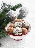 在一个白色陶瓷碗的被分类的自创黑暗的块菌状巧克力,圣诞树和圣诞节装饰的分支 免版税库存图片