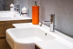 在一个白色水槽的豪华搅拌器在一个美丽的灰色卫生间里 免版税库存图片