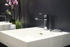 在一个白色水槽的豪华龙头搅拌器在一个美丽的灰色卫生间里 图库摄影