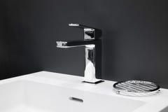 在一个白色水槽的豪华龙头搅拌器在一个美丽的灰色卫生间里 库存图片