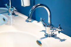 在一个白色水槽的豪华龙头搅拌器在一个美丽的蓝色卫生间里 库存照片