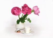 在一个白色水罐和一杯咖啡的桃红色玫瑰 库存照片
