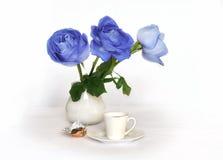 在一个白色水罐和一杯咖啡的蓝色玫瑰 库存照片